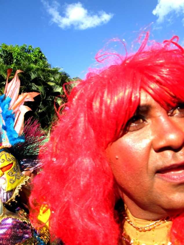 A traditional travestí (transvestite) looks out to the crowd. Although in more elaborate carnivals (like in the Capital and other countries), well-known trans women performers in burlesque costumes have taken the place of the travestís, in DR they often use their schtick to make light of notorious stereotypes of women in the country. La Chapiadora (the ubiquitous Dominican Golddigging female) is a popular character to enact. Photo by José Germosén