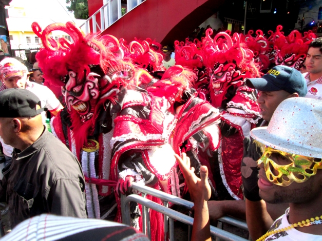 "La Vega's premiere club exits the traditional ""cave"" of Vegan Carnaval. They represent the official face of Los Diablos Cajuelos in La Vega. Lucky club members get to pre-game to blaring merengue inside the cave alongside Los Diablos before they make their ascent onto Avenida España."